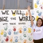 Samantha Mendoza with her hands up in front of a hand print wall
