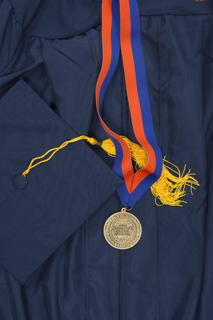 SU Scholars medal with graduation cap and gown