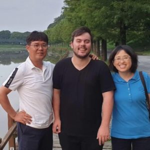 three people pose for a picture, standing in front of a lake. They are all smiling.
