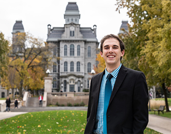 a man stands in front of a gothic building. He is smiling and wearing a suit.