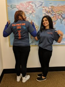 two women stand in front of a picture of a map. One has her back to the camera, and one her front. Both are smiling and giving thumb's up. They are wearing new CFSA blue tshirts.