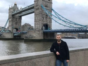 Zach Watson stands leaning on a wall in front of the Thames River in London, England. The London Bridge can be seen in the background, as well as a cloudy, grey sky.