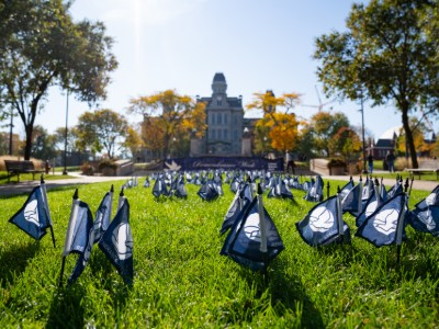 closeup of small flags signifying those who passed away in Pan Am 103 are placed in the grass overlooked by a large gothic building.