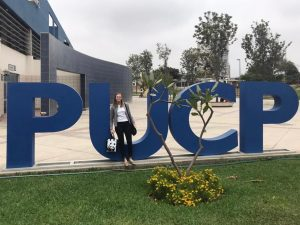 "woman sitting on a letter ""U"" in a large outdoor sign that spells ""PUCP"""