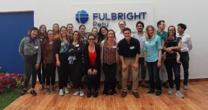 "large group of people standing in a building in front of a sign that reads ""Fulbright Peru."""