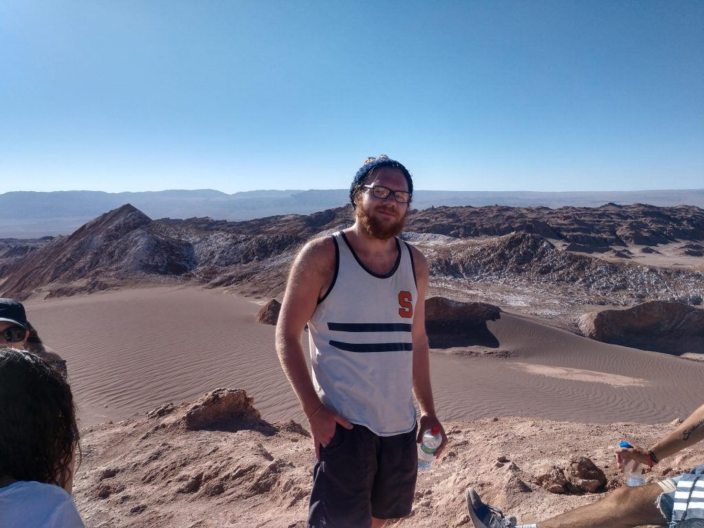 white man standing in a desert and smiling. He is wearing an SU tanktop