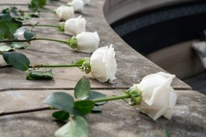 close up image of white roses on wall of remembrance