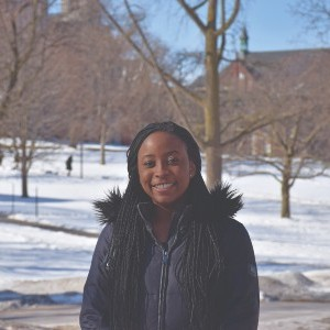 woman stands smiling at the camera outside in front of a snowy winter landscape.