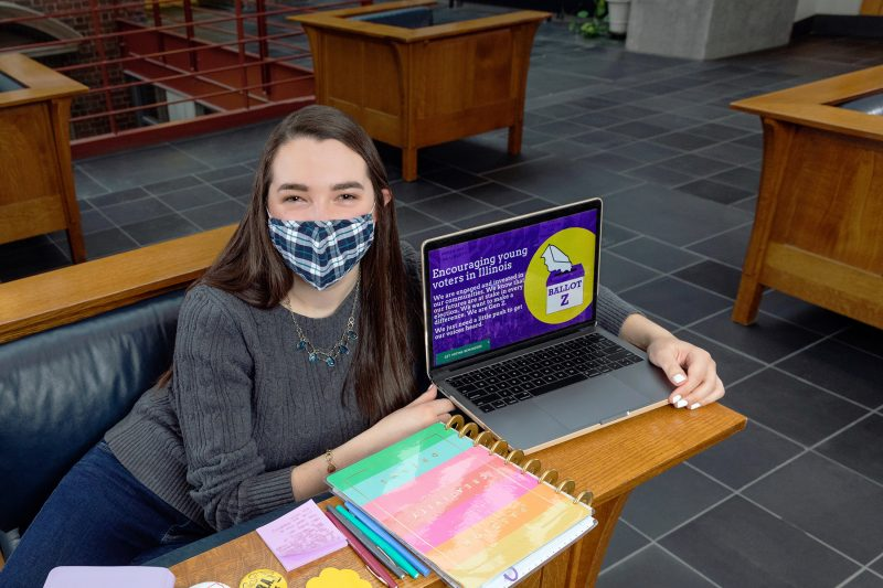 Woman in mask sits in front of computer and notebooks