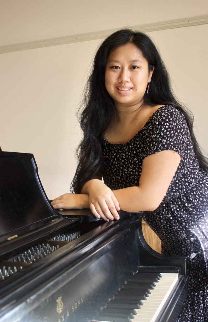 A woman with long brown hair leans smiling over the edge of a piano.