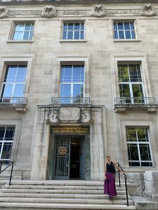 """Woman stands in front of grey stone building that reads """"London School of Hygiene and Tropical Medicine"""""""